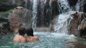à beira da piscina : Couple bathing by waterfall in embracing and hugging romantic in natural beautiful pool in tropical travel destination.