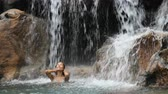 praní : Sexy beautiful multicultural woman bathing under waterfall in bikini on vacation travel. Pretty mixed race girl in pristine nature enjoying summer travel vacation. SLOW MOTION. 59.94 FPS,