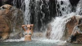 мыть : Sexy beautiful multicultural woman bathing and swimming under waterfall in bikini on vacation travel. Pretty mixed race girl in pristine nature enjoying summer travel vacation.