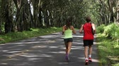 dışarı : Runners running on forest road. Sport fitness couple jogging exercising together. Back view. 59.94 FPS SLOW MOTION. Stok Video