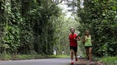 floresta : Couple running on forest road on Kauai, Hawaii, USA. Woman and man jogging on forest path with eucalyptus trees in beautiful hawaiian nature landscape.