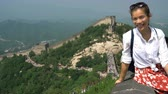 badaling : Great Wall of China. Woman tourist on travel waving hand saying hello to camera by famous Chinese tourist destination and attraction in Badaling north of Beijing. Woman traveler on vacation. Stock Footage