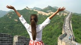 badaling : Happy cheerful tourist woman at Great Wall of China having fun free in freedom pose with arms up on travel during vacation trip in Asia. Girl visiting and sightseeing Chinese attraction in Badaling Stock Footage