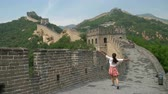 badaling : Fun happy cheerful joyful tourist woman at Great Wall of China on travel smiling laughing and dancing during vacation trip in Asia. Girl visiting and sightseeing Chinese attraction in Badaling