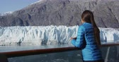 stateroom : Tourist on cruise ship travel in Alaska looking at glacier in Glacier Bay National Park and Preserve, USA. Woman cruising Inside Passage enjoying stateroom balcony with view of Margerie Glacier.