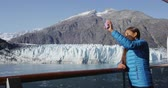 varanda : Alaska cruise ship passenger taking selfie photo in Glacier Bay National Park, USA. Woman tourist taking picture using smart phone on travel vacation. Margerie Glacier. Stock Footage