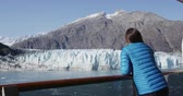 stateroom : Glacier Bay Alaska cruise ship passenger looking at glacier in Glacier Bay National Park, USA. Woman on travel sailing Inside Passage enjoying luxury stateroom balcony with view of Margerie Glacier. Stock Footage