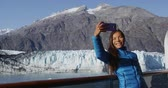 passagem : Tourist on Alaska cruise ship passenger taking selfie photo in Glacier Bay National Park, USA. Woman tourist taking picture using smart phone on travel vacation. Margerie Glacier. Vídeos