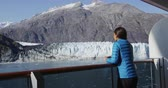 varanda : Tourist on Alaska cruise ship looking at glacer in Glacier Bay National Park, USA. Woman on travel vacation sailing enjoying view of Margerie Glacier.