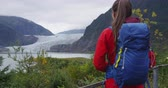alasca : Hiking woman wearing hiker backpack in Alaska nature looking at glacier landscape. Woman on travel adventure enjoying view of Mendenhall Glacier.