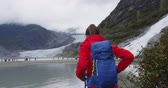 alasca : Hiking woman wearing hiker backpack in Alaska nature looking at glacier landscape. Woman on travel adventure enjoying view of Mendenhall Glacier and lake and Nugget Falls waterfall.