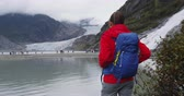 alasca : Hiker woman wearing hiking backpack in Alaska nature looking at glacier landscape. Woman on travel adventure enjoying view of Mendenhall Glacier and Nugget Falls waterfall. Vídeos