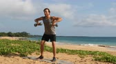 instrutor : Fitness man exercising doing Standing Dumbbell Upright Row exercise on beach. Male athlete showing exercises. Traps workout outdoors on beach.