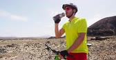 sedento : Mountain biking MTB man drinking water resting from cycling on bike trail. Male mountain biker on bike riding bicycle enjoying healthy active lifestyle in nature. SLOW MOTION.
