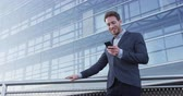 sorridente : Phone. Business man using phone sms texting using app on smartphone in city business district. Young businessman using mobile phone smiling happy in suit jacket outdoors. Urban male professional Stock Footage