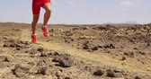 pustynia : Running man trail running in desert - male athlete runner running fast. Close up of running legs and running shoes with dust and rocks flying in SLOW MOTION. Wideo