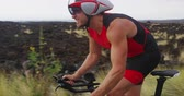 profesionální : Triathlon man cycling - male triathlete biking on triathlon bike. Cyclist on professional triathlon bicycle wearing time trail helmet for ironman race. From Big Island Hawaii. SLOW MOTION