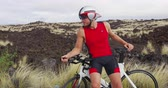 trial : Triathlon cycling concept - Triathlete portrait of man with triathlon bike. Fit cyclist man on professional triathlon bicycle wearing time trail helmet for ironman race. From Hawaii. SLOW MOTION. Stock Footage