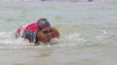 rastejar : Triathlon swim. Male triathlete swimmer man running out of ocean after swimming finishing swimming. Fit man ending swimming sprinting out of water in professional triathlon suit training for ironman.