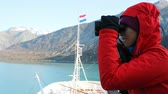 varanda : Tourist looking at Alaska Glacier Bay landscape using binoculars on cruise ship. Woman on vacation travel looking for wildlife enjoying cruising famous tourist destination.  SLOW MOTION.
