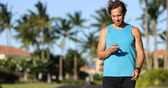 móvel : Fitness man looking at smart phone fitness app after running. Active athlete looking at smartphone app after cardio workout for pace, distance and heart rate data and information.