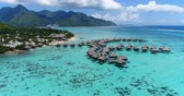 wyspa : Tropical vacation paradise island with overwater bungalows resort in coral reef lagoon ocean by beach. Aerial video of Moorea, French Polynesia, Tahiti, South Pacific Ocean.
