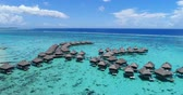 helicóptero : Travel vacation paradise aerial video with overwater bungalows in coral reef lagoon sea. Aerial video from French Polynesia, Tahiti, South Pacific Ocean. Stock Footage