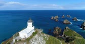 pontos : New Zealand nature landscape aerial drone footage with people sightseeing Nugget Point Lighthouse in Otago region and peninsula on South Island. Beautiful tourist destination and attraction from above