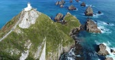 visto : New Zealand aerial drone footage of Nugget Point Lighthouse in Otago region and peninsula on South Island of New Zealand. Beautiful tourist destination and attraction seen from above.