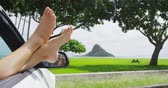 perna : Relaxing vacation car road trip travel with feet out the window. Convertible car holiday concept with female legs in front of Oahu landmark : Chinamans Hat in Hawaii, USA. Stock Footage