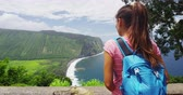 рюкзак : Hawaii landscape - Woman tourist looking at Waipio Valley Lookout view on Big Island, Hawaii. Iconic Hawaiian nature at famous tourist destination on Big Island, Hawaii, USA. Стоковые видеозаписи