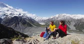 cracker : Hiking couple taking break eating food on alpine hike by Mount Cook New Zealand. Happy young people backpacking and tramping in Aoraki  Mt Cook National Park.