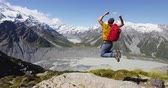 desafio : Hiking man jumping of joy in winning cheering in success concept on New Zealand. Adventure outdoors tramping.backpacker cheering at view of Mt Cook in Aoraki  Mount Cook National Park.