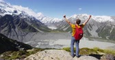 desafio : New Zealand hiker travel nature hiking man winning with arms up in success. Adventure outdoors tramping backpacker cheering at view of Mt Cook in Aoraki  Mount Cook National Park. Stock Footage