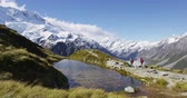 excursão : Hiking travel nature hikers in New Zealand mountains. Couple people walking on Sealy Tarns hike trail route with Mount Cook landscape, famous tourist attraction. Vídeos