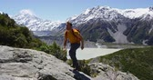 colina : Hiker hiking scrambling on adventure climbing up mountain on hike in amazing nature landscape. Man tramping and trekking by view of Mt Cook in Aoraki  Mount Cook National Park. Stock Footage