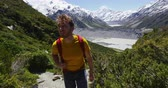orientar : Hiking man in New Zealand mountains on Mount Cook trail with snow capped mountain peaks. Happy hiker walking in nature landscape.