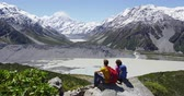 mountain : Hiking couple looking at view. Active hikers outdoors in mountains relaxing enjoying resting during hike. Young couple on trail by Mt Cook in Aoraki  Mount Cook National Park.