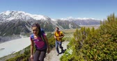 casal : Hiking travel people in New Zealand. Couple people walking on Sealy Tarns hike trail route in Mount Cook national park landscape, a famous tourist attraction.  SLOW MOTION. Vídeos