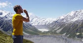 rega : Man drinking water hiking in front of Mount Cook in New Zealand. Male hiker enjoying drinking water from water bottle in amazing landscape in Aoraki  Mt Cook National Park. Stock Footage