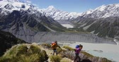 pista : Hiking travel nature hikers in New Zealand. Couple people walking in Mount Cook National Parks hike trail route, a famous tourist attraction. SLOW MOTION. Stock Footage