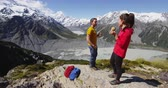 cracker : Hiking couple taking food break on alpine hike in New Zealand by Mount Cook eating sandwich. Happy young people backpacking and tramping in Aoraki  Mt Cook National Park.