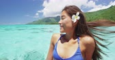 fundo : French polynesia tahiti flower woman relaxing on ocean portrait. Happy Asian girl sunbathing on tropical ocean water background sun tanning in swimsuit. SLOW MOTION.