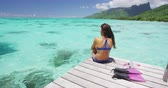 barbatanas : Summer vacation watersport girl lifestyle woman relaxing on overwater resort deck in peaceful destination in serenity. Tropics travel vacations.