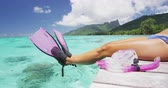 barbatanas : Travel vacation snorkel girl relaxing with legs over water on holiday villa deck. Snorkeler having fun on overwater bungalow at luxury travel resort playful doing funny feet with pink snorkel fins. Vídeos