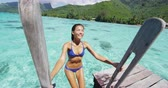 Сейшельские : Bikini swimming woman coming from ocean swim in tropical paradise destination in luxury travel resort. Sexy woman enjoying holidays on overwater deck at hotel in Tahiti, French Polynesia. Стоковые видеозаписи