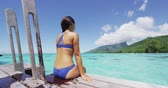 varanda : Bikini woman enjoying tropical vacation sitting after swim on overwater bungalow resort deck at luxury hotel in Tahiti, French Polynesia. Summer tropical holidays lifestyle. SLOW MOTION. Stock Footage