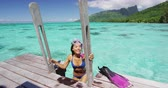 nadador : Swimming girl coming out of water after snorkel swim in coral reefs of Tahiti ocean on private deck of overwater bungalow in Moorea, French Polynesia. Happy Asian girl. Luxury travel lifestyle.