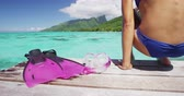 коралловый : Girl having fun doing watersport snorkel swim activity in tropical ocean on beach summer holidays. Bikini woman arriving from swim sitting on deck of overwater bungalow next to snorkeling mask, fins.