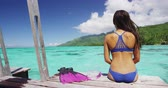 nadador : Bikini woman on tropical travel sitting on overwater bungalow deck of luxury resort after snorkel swim in Tahiti ocean. Girl enjoying French Polynesia vacations. Stock Footage